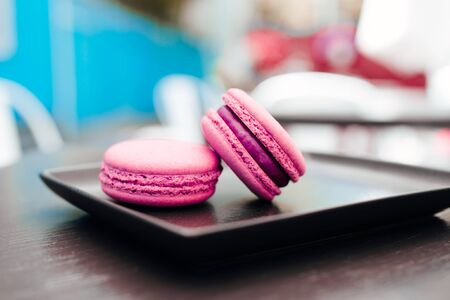Sweet, fresh macarons with coffee in a blue cup on a black table