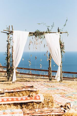 Arch decorated with lively floristics on the background of the sea. Boho style