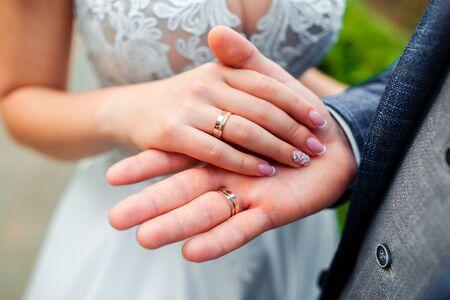 Trouwringen in de handen van de bruid en bruidegom.