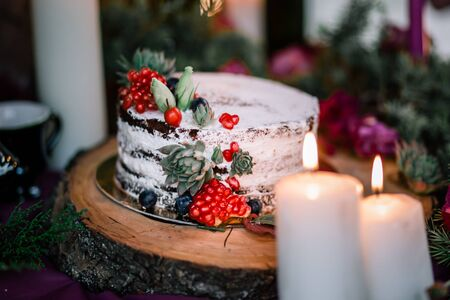 Delicate wedding white cake decorated with pomegranate and succulent surrounded by flowers.-Image Imagens