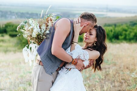 The groom dressed in the style of boho gently kisses the bride.
