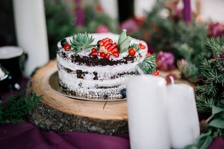 Delicate wedding white cake decorated with pomegranate and succulent surrounded by flowers and candles.