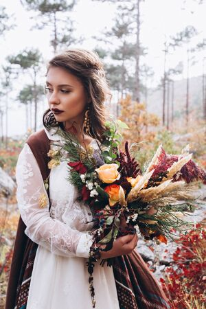 Wedding floristry in a yellow autumn meadow in the hands of a girl dressed in the style of boho.