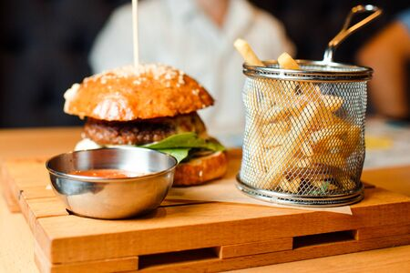 French fries and hamburger on a wooden plate. View from above.