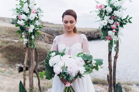 Bride with a wedding bouquet of white roses in hands.