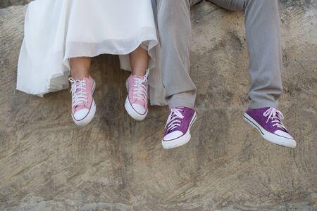 Das Brautpaar mit lila und rosa Turnschuhen.