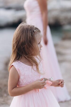 Mother and daughter on a cliff and look at the sea in pink dresses.