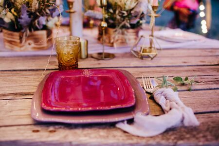 Romantic dinner on a wooden table with burgundy plates and fresh flowers. Stock fotó