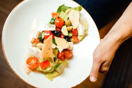 Greek salad in an original serving on a dish. Tomatoes, cheese, vegetables. Stock Photo