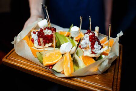 Fruit sliced pomegranate, orange and kiwi in a restaurant.