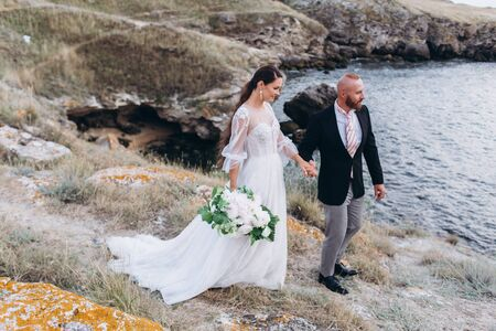 The bride and groom hugging and kissing on the background of the sea and rocks. Stock Photo