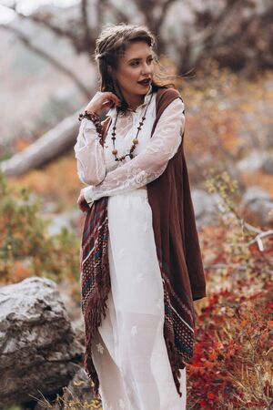 Girl in boho style on a background of autumn forest. Stock Photo