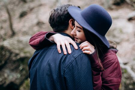Girl in a hat hugs a guy with tenderness. Stock Photo