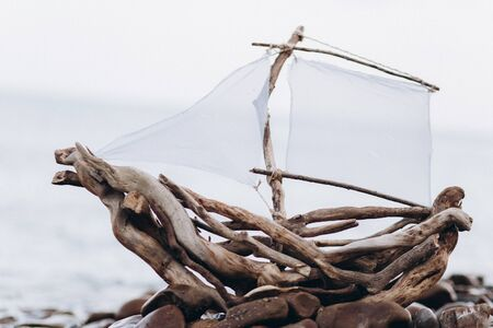 Decorative ship made of branches and roots with a sail on the seashore. Stock Photo - 128377144