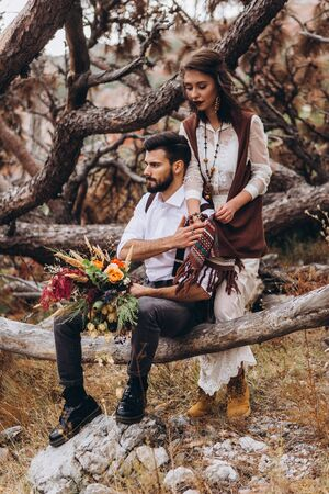 Stylish guy with a beard hugs a girl dressed in a dress in the style of boho. Reklamní fotografie