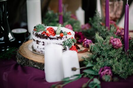 Delicate wedding white cake decorated with pomegranate.