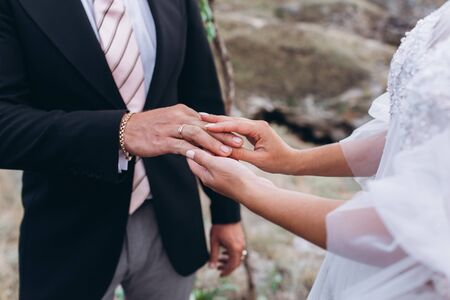 Wedding rings in the hands of the bride and groom. Stock Photo - 128377096