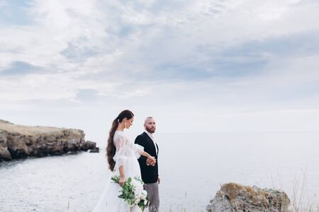 The bride and groom hugging and kissing on the background of the sea and rocks. Stock Photo - 128377093