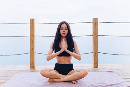 Girl practicing yoga while sitting by the sea on a wooden floor.