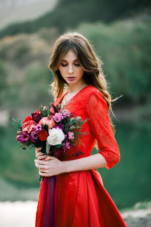 Young bride in a red dress with an Assemtric bouquet of pomegranates and roses.