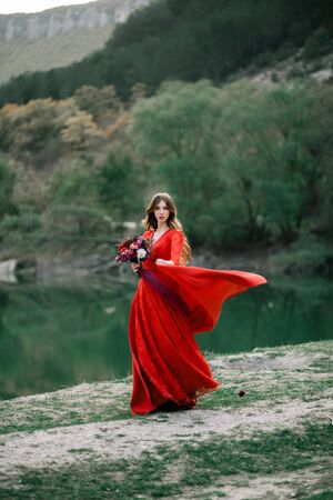 Young bride in a red dress with an Assemtric bouquet of pomegranates and roses. Stock Photo - 128377058