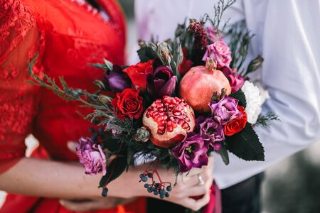 Wedding asymmetrical stylish bouquet with red roses and pomegranate.