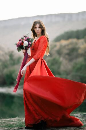 Young bride in a red dress with an bouquet of pomegranates and roses.