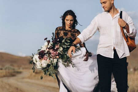 Wedding couple in love in boho style. Asymmetric bouquet of roses.