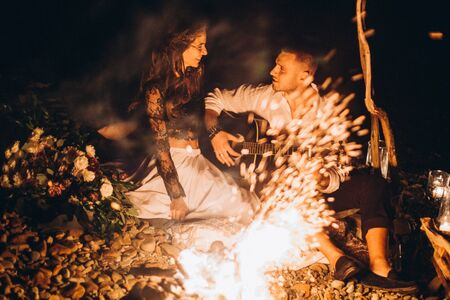 Guy and Girl on a romantic date in the evening around the fire.