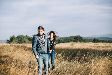 Girlfriend and boyfriend hold hands together, walk in the field.