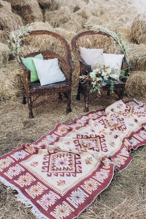 Wedding asymmetrical stylish bouquet with roses on a boho wicker chair.-Image