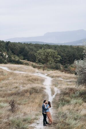 Boyfriend and Girlfriend run in tall yellow grass in the forest.