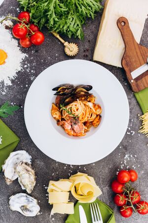 Pasta with king prawns on a gray background in a white dish.