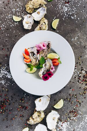 Oysters on a dish decorated with flowers on a gray background. Aphrodisiacs.