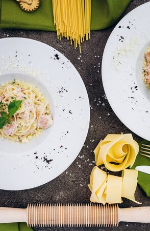 Spaghetti with olive color embellished with greenery, rolling pin, pasta. Banco de Imagens
