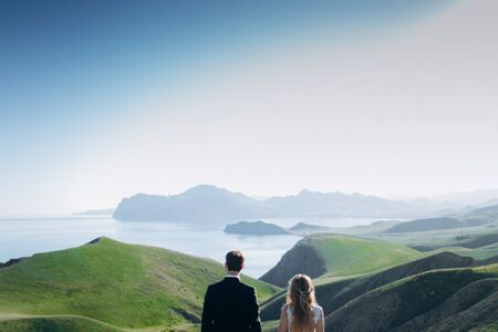 Loving girl and guy look at the mountains and the sea. Stock Photo