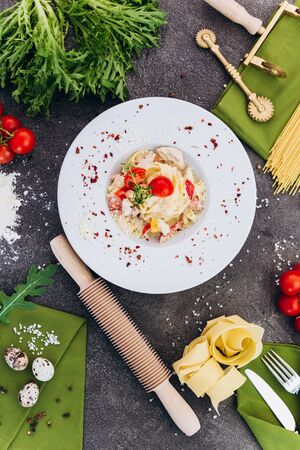 Pasta made of spaghetti on a gray background with decorations for advertising the menu. Banco de Imagens