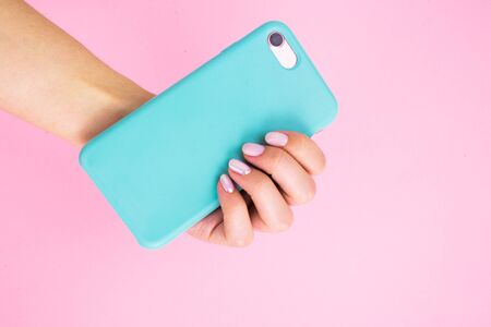 Smartphone in a mint case in hand with manicure on a pink background.
