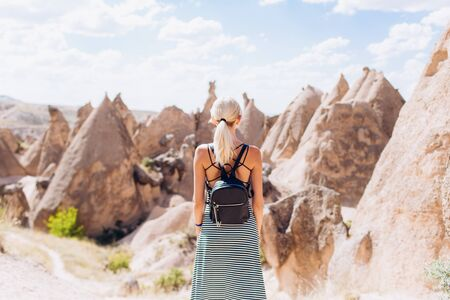 A blonde girl runs across the mountains in Turkey in Cappadocia. Follow me. Banco de Imagens
