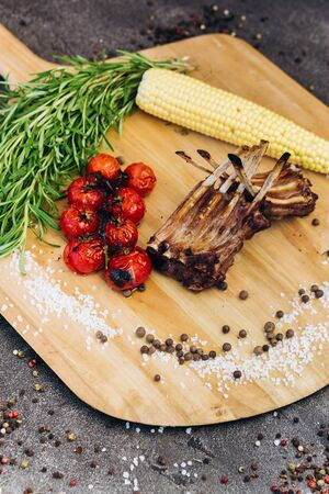 Meat ribs with vegetables on a wooden Board with herbs.