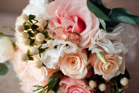 Pale pink bridal bouquet with delicate pink flowers with rings.