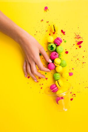 Colored, bright, sweet macaroons on a yellow background. Antigravity. Asymmetry.