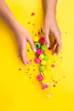 Scattered macaroons from a glass on a yellow background. Colored, bright, sweet macaroons on a yellow background.