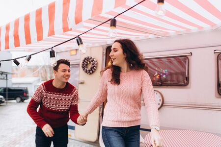 Loving couple run to meet Christmas on the background of a road trailer.