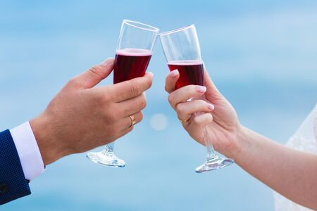 Glasses with red champagne in hands on a background of the sea.