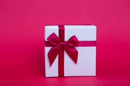 New Years white gift with a red ribbon and bow on a red background. Stockfoto