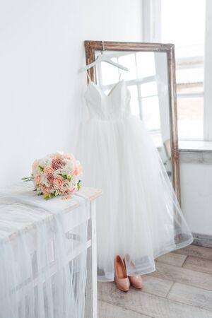 Landschaft für den Morgen der Braut mit einem weißen Hochzeitskleid und einem Blumenstrauß.