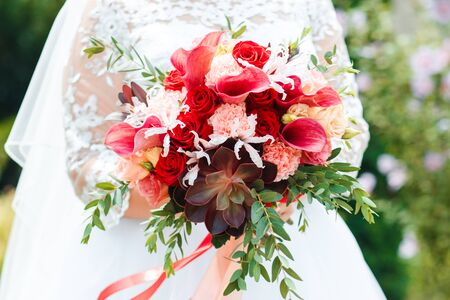 Red bridal bouquet of peonies and roses. Scenery for the wedding.