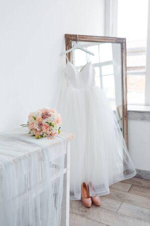 Landschaft für den Morgen der Braut mit einem weißen Hochzeitskleid und einem Blumenstrauß. Standard-Bild