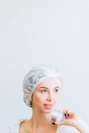 A young girl with well-groomed skin in a hat is holding a jar of cream in her hands. Place for text. Personal care.